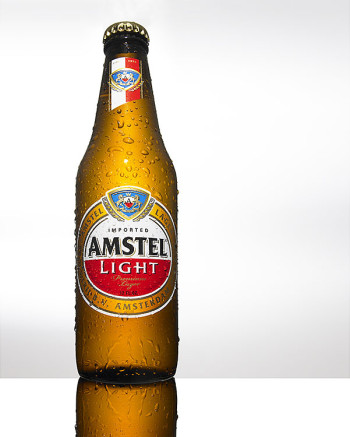 PHOTOGRAPH OF AMSTEL LIGHT BOTTLE ON A WHITE GREY BACKGROUND PHOTOGRAPHED BY THEBEHRENS.NYC DENISE BEHRENS RAINER BEHRENS