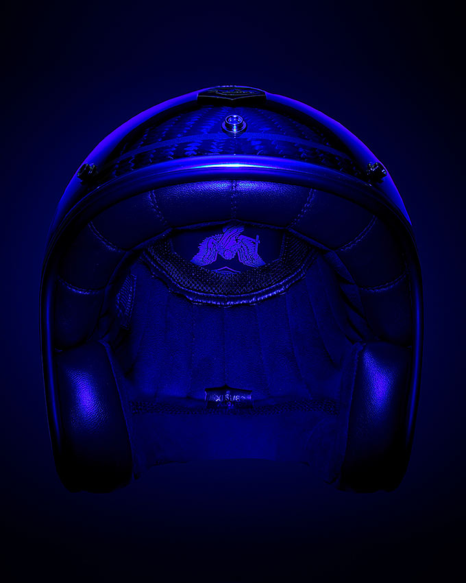PHOTOGRAPH OF RUBY MOTORCYCLE HELMET ON A BLACK BACKGROUND